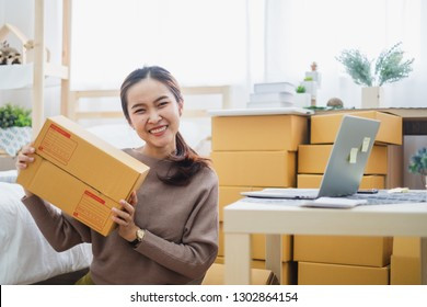 Young asian woman seller showing box package for online business, online shopping, shipping, concept.