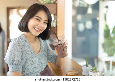young asian woman short hair in sky dress holding a cup of ice frappe chocolate , young woman smiling