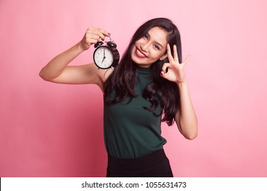 Young Asian woman show OK with a clock on pink background