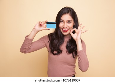 Young Asian woman show OK with a blank card on beige background