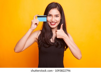 Young Asian woman show OK with a blank card on yellow background