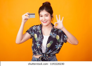 Young Asian woman show OK with a blank card in  tropical shirt on yellow background