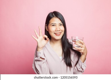 Young Asian woman show OK with a glass of drinking water on pink background
