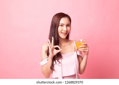 Young Asian woman show OK  with orange juice on pink background
