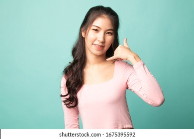 Young Asian woman show with phone gesture on cyan background