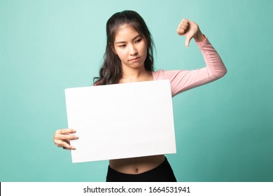 Young Asian woman show thumbs down with white blank sign on cyan background