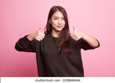 Young Asian woman show two thumbs up on pink background