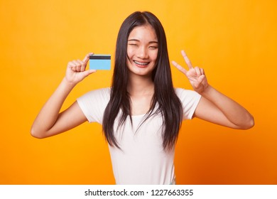 Young Asian woman show Victory with a blank card on bright yellow background
