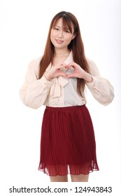 Young asian woman showing a heart symbol with her fingers