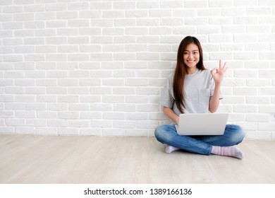 Young asian woman showing ok hand sign and smiling while working with laptop computer in white room with copy space, people with positive gesture