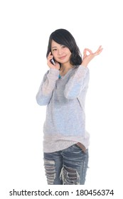 Young Asian woman showing OK gesture and talking with smart phone.