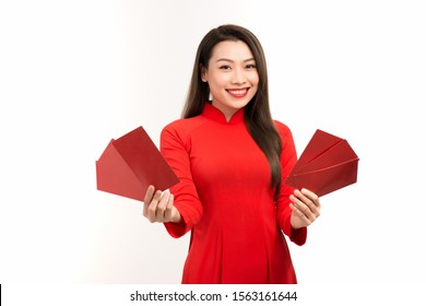 Young Asian woman showing red envelope for lunar new year while wearing Ao Dai over white background.