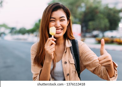 Young Asian woman showing thumbs up with popsicle ice cream in outdoor scene. Female with good teeth health