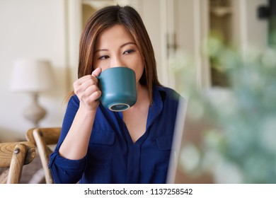 Young Asian woman sitting alone at a table at home working on a laptop and drinking a cup of coffee