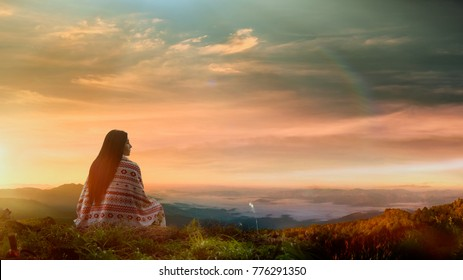 Young asian woman sitting alone outdoor with wild forest mountains on background.