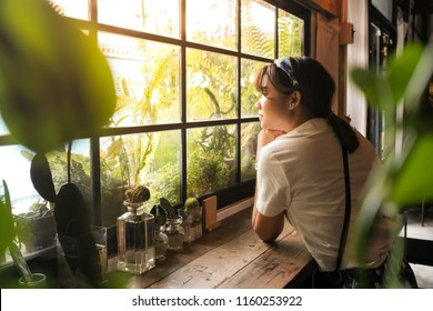 Young asian woman sitting in the cafe and thinking while looking out of the window in the cafe