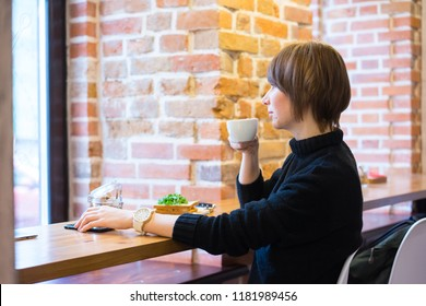 Young asian woman sitting at the cafe drinking coffee