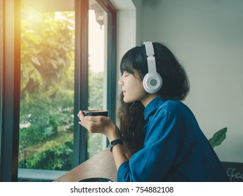 Young asian woman sitting in cafe; Relaxed and listening music; Tablet and coffee cup on side in coffee shop.