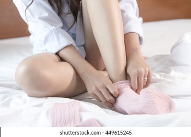 Young Asian woman sitting on a bed wearing socks.
