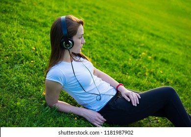 Young asian woman sitting and relaxing on fresh spring grass in garden listening to music on her mobile phone smiling with pleasure. Beautiful female expecting child having rest outside in park.