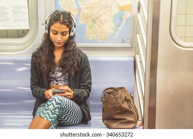 Young asian woman sitting in a subway car and listening music with her smartphone - Pretty girl riding on a train and going to work