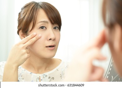 Young asian woman with skin problems, looking at herself reflected in a mirror.