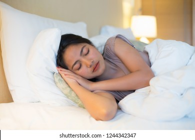 Young asian woman sleeping in white bed with happiness