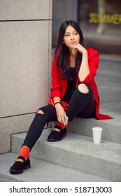 Young Asian woman with smartphone sitting on steps against mall. Fashion business photo of beautiful girl in red casual suite with phone and cup of coffee