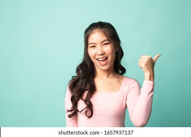 Young Asian woman smile and point to copy space with her thumb on cyan background