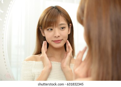 Young asian woman softly touching her cheeks, she is looking at her reflection in a mirror.