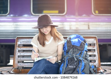 Young Asian woman is solo travel by train and looking with taking note on the travel map in the station.