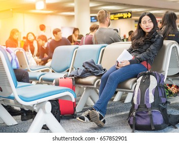 Young Asian woman solo traveler waiting for flight travel at airport terminal