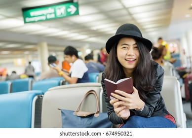 Young Asian woman solo traveler holding passport and waiting for flight travel at airport terminal