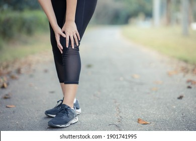 A young Asian woman sore knees after running.