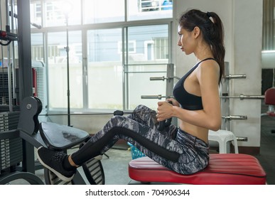 Young asian woman in sportswear workout training with machine.