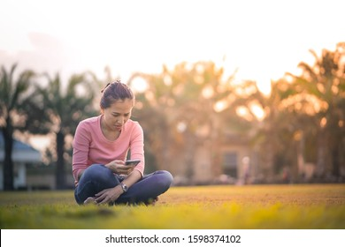 Young asian woman squatting down on green grass field using and looking at smartphone alone, pretty woman sitting in a park typing on mobile phone by herself, space for text and design