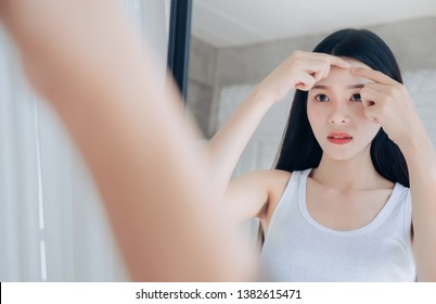 Young Asian woman squeeze acne problem face looking at mirror.