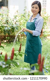Young Asian woman standing in apron holding hosepipe and watering plants outdoors