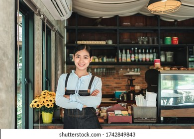 Young asian woman standing in front of coffee cafe counter shop owner. cross hands.