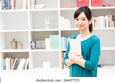 young asian woman standing front of book shelf