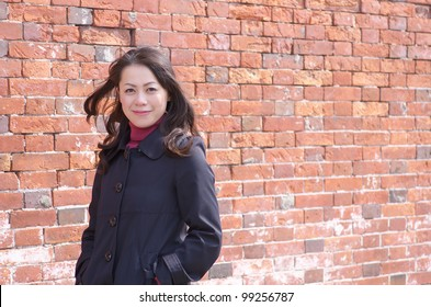 Young Asian woman standing in front of brick wall