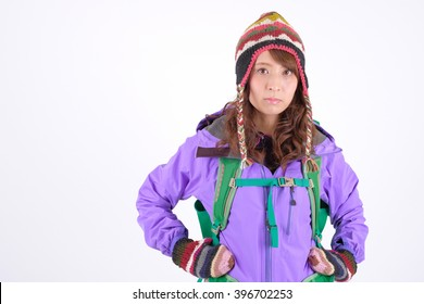 Young Asian woman standing in the studio while carrying a hiking bag and smiling at the camera, isolated on white background