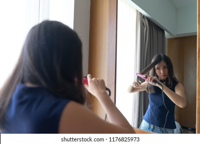 Young Asian woman straightening hair with hair straightener flat iron while looking into the mirror at home. Beautiful girl lifestyle, beauty concept.