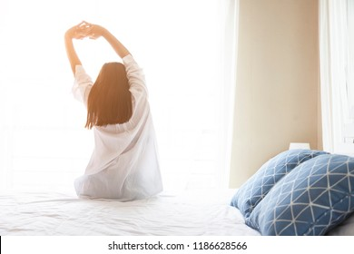 Young Asian woman stretching in bed after wake up, back view having a good day,sunlight in morning. I am preparing to go to work or university or happy holiday. lifestyle start up to beautiful day