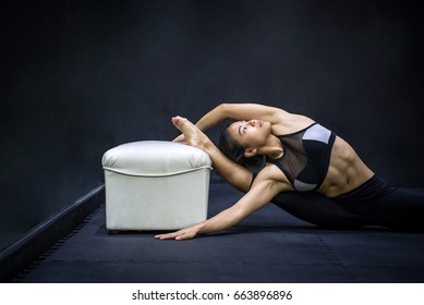 Young Asian woman stretching with chair in the fitness gym, yoga exercise warm up, sport and training lifestyle concept