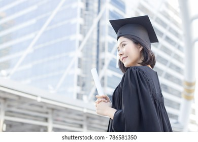 Young Asian Woman Students wearing Graduation hat and gown at University, Woman Students  with Graduation Concept.