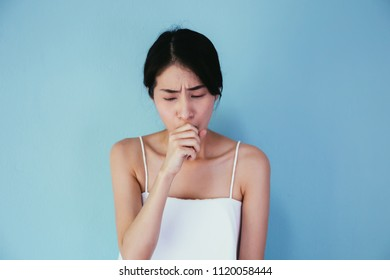 Young Asian woman suffering from cough / lung or throat problems isolated over blue background - Healthcare and Medical concept
