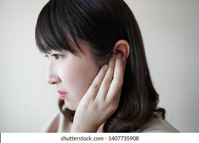Young asian woman suffering from ear pain and tinnitus. Cause of earache includes otitis, earwax buildup, a foreign object in the ear, sinus infection or changes in air pressure. Ear disease concept.