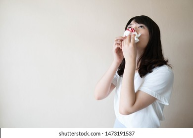 Young asian woman suffering from nose bleeding and using tissue paper for stop bleeding over white background. Cause of nosebleed inclued allergic rhinitis, respiratory infection or hypertension.