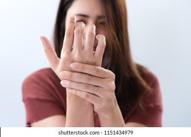 Young asian woman suffering from pain in palms. Female massaging her painful hand from symptoms of Peripheral Neuropathy. Pain and numbness in fingertips and palms. Health care and physical concept.